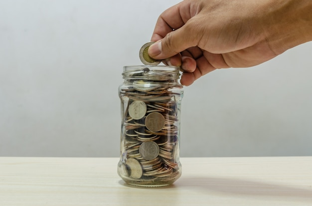 Hand holding a coin into a glass jar. business concept of saving money. financial and investment planning for the future.