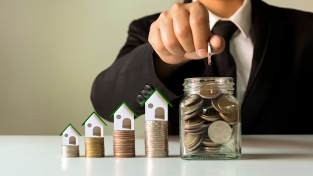 Hand holding coins in a jar for saving money and house designs on piles of coins