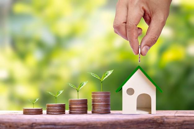 Рука держит монеты, помещенные в модель дома для экономии денег, и деревья, растущие на куче денег