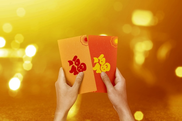 Hand holding colorful envelopes (angpao) with blurred light wall. happy chinese new year