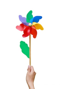 Hand holding colorful pinwheel over white background