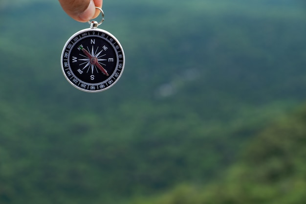 Hand holding compass against green tree montain background.