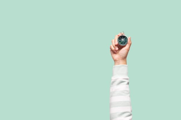 Hand holding compass on green background