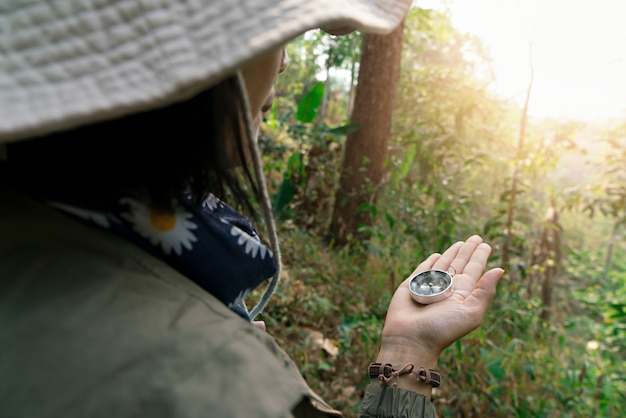 Hand holding compass for planning hiking and adventure