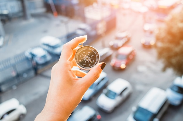 Hand holding compass above street with cars