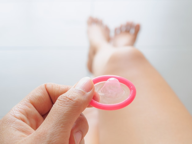 Hand holding condom and sexy legs