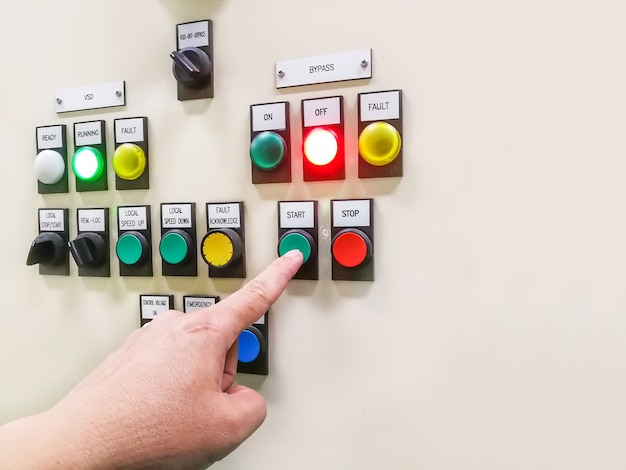Hand holding the control panel of the industrial plant and pushing or turning the button in electrical selector switch,button switch motor control center cabinet