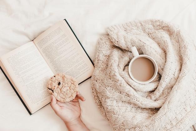 Рука с печеньем на книгу возле горячего напитка в плед