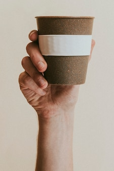 Hand holding a cork reusable cup