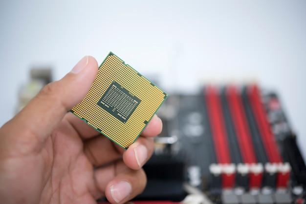 Cpuを持っている手は、ic表面を表示し、白いbakcgroundに分離されたcpuのマザーボードオープンソケットマウントを持っています。