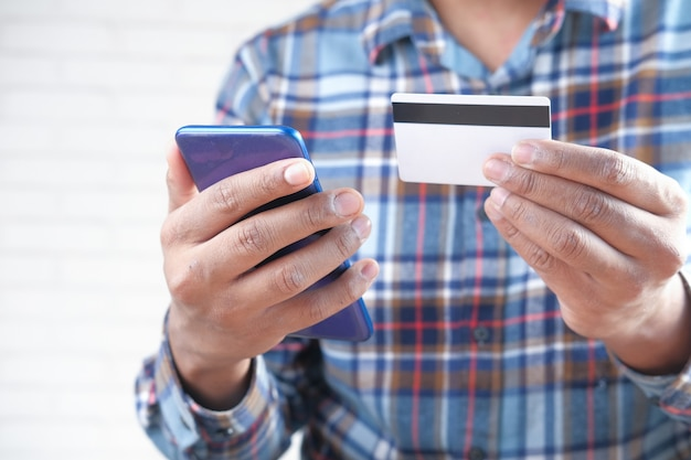 손을 잡고 신용 카드와 스마트 폰 온라인 쇼핑