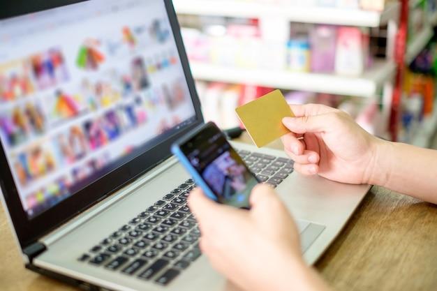 신용 카드를 들고 온라인 결제를 위해 스마트폰으로 노트북 사용