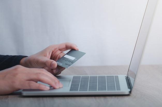 クレジットカードを持って、ラップトップを使用している手。