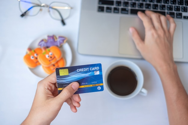 ハロウィーンのクッキーとコーヒーを食べている間、ラップトップでオンラインショッピングのためのクレジットカードを持っている手。ハッピーハロウィン、こんにちは10月、秋秋、お祭り、パーティー、休日のコンセプト