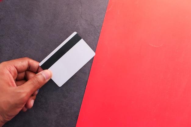 Рука кредитной карты на цветном фоне.