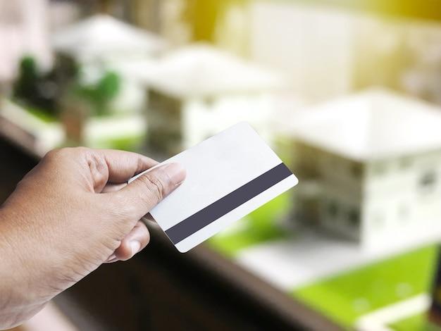 不動産と建築のビジネスコンセプトの棚の上の家モデルのサンプルの抽象的なぼやけた上にクレジットカードを持っている手。モンタージュスタイル。