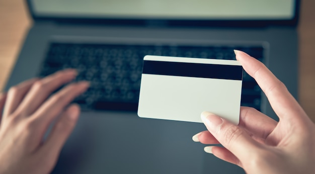 Hand holding credit card and press laptop computer enter the payment code for the product.