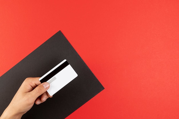 Hand holding a credit card on red background