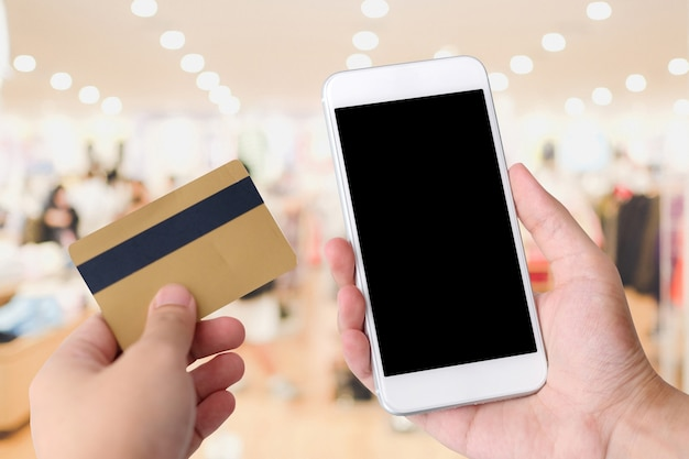 Hand holding credit card and smart phone with blank on screen background