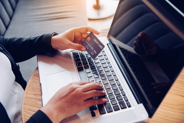 Hand holding a credit card in their hands and find information about a product using their laptop device to make purchases online and conduct financial transactions.