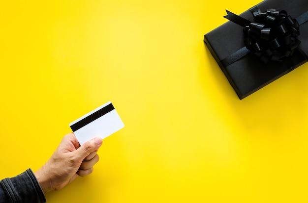블랙 프라이데이와 사이버 먼데이 컨셉을 위해 노란색 바탕에 검은색 선물 상자를 사기 위해 신용 카드를 들고 있습니다.