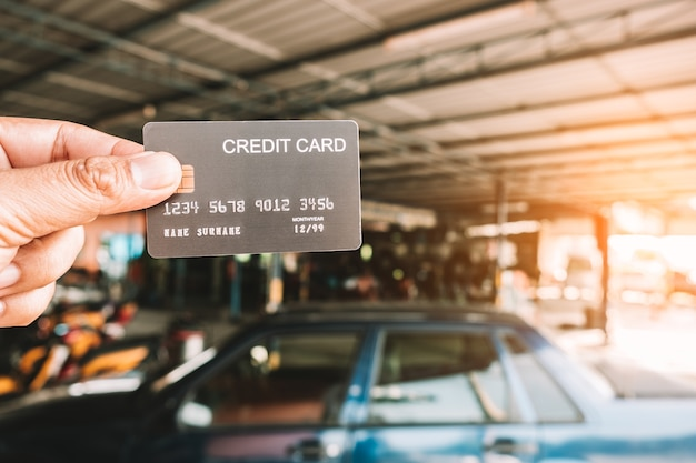 Hand holding a credit cards at auto repair shop