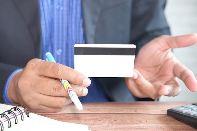 情報を読むクレジットカードを持っている手。