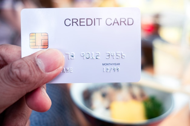 Hand holding a credit cards at restaurant