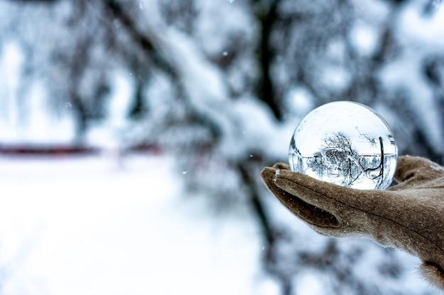 Рука, держащая хрустальный шар в снежном пейзаже
