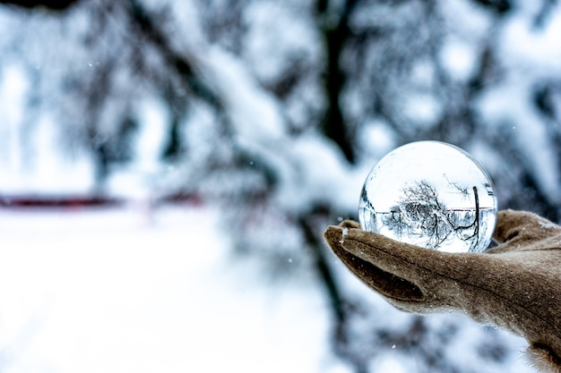 Hand holding crystal ball in a snowy landscape