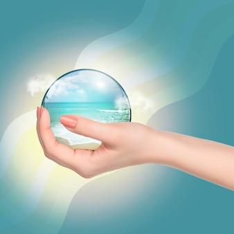Рука, держащая хрустальный шар с тропическим пляжем и морем