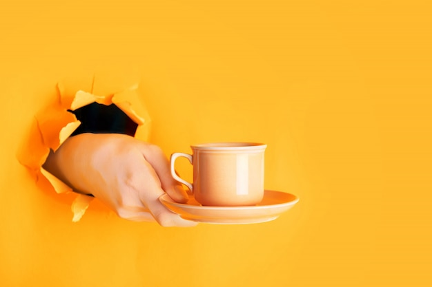 Hand holding a cup of coffee through a hole in torn saffron or light orange paper wall