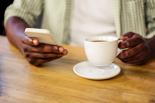 Hand holding a cup of coffee while using a smartphone