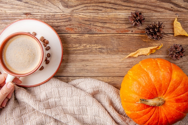 Hand holding cup of coffee on wooden background with pumpkin