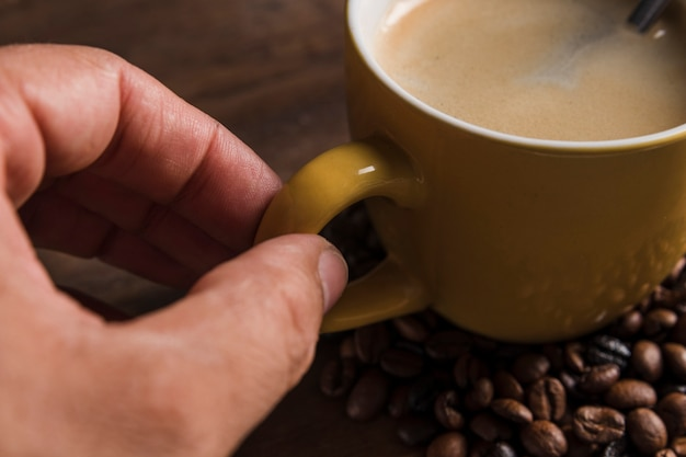 Hand holding cup handle with coffee