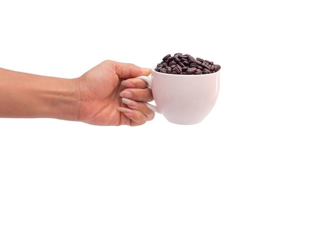 白い背景で隔離のコーヒー豆のカップを持っている手