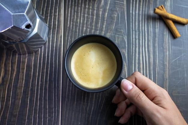 나무 테이블 상위 뷰 위에 손을 잡고 커피 한잔