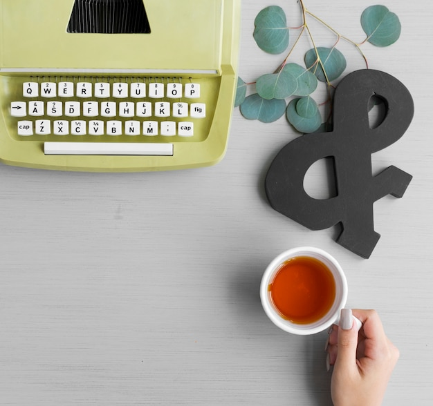 A hand holding a cup of tea featuring a retro typewriter