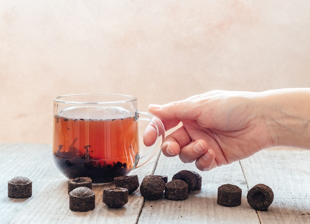 A hand holding a cup of traditional chinese puer tea with aged puerh tea bricks on wooden table, brewing of pu-erh sachets