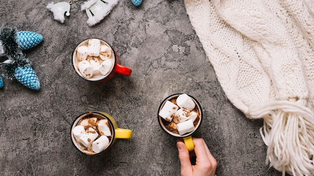 Hand holding cup with marshmallows near mugs, christmas toys and knitted scarf