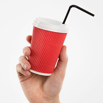 Рука держит чашку с соломой