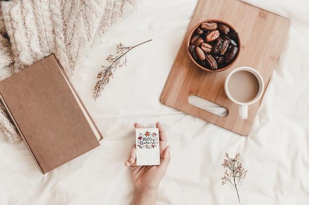 Рука, держащая вырез возле еды и книги на кровати