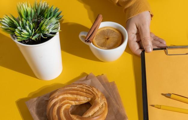 フォーチュナゴールドイエロー色の背景、上面図のお茶またはホットワインとケーキの近くにcvを持っている手。