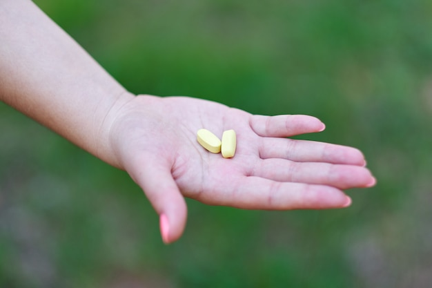 Hand holding daily supplements, vitamins or medication
