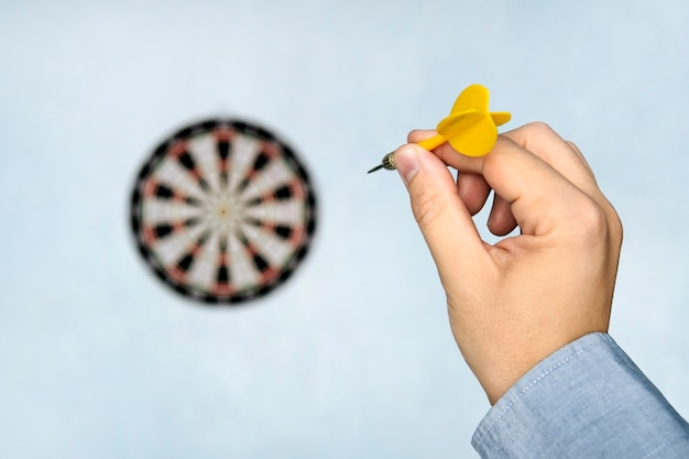 A hand holding a dart getting ready to aim at the dartboard on blue wall. a man's hand throws a dart at the target.