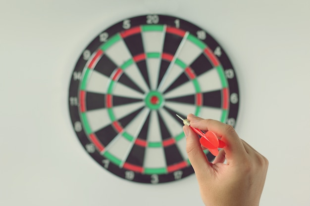 A hand holding a dart getting ready to aim at the dartboard on white wall