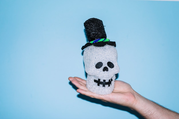 Hand holding decorative skull in hat