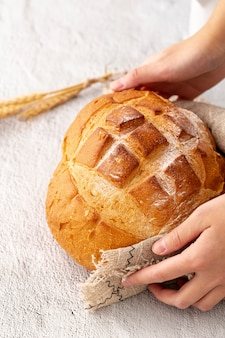 Hand holding delicious baked bread and hessian cloth