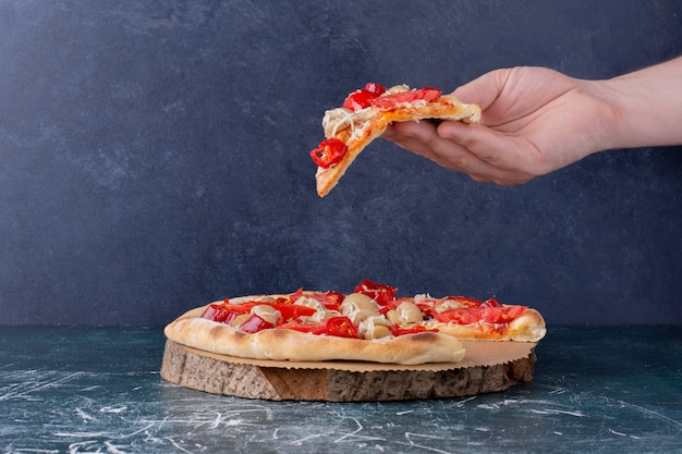 Hand holding delicious chicken pizza with tomatoes on marble.