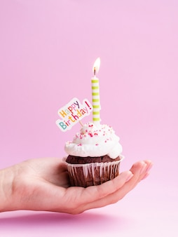 Hand holding delicious muffin with happy birthday sign